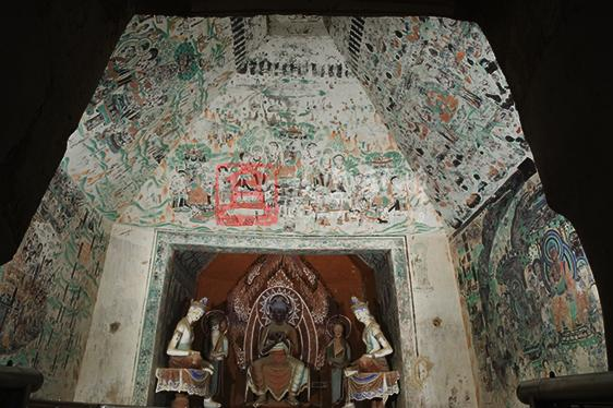 Located in the middle section of the Southern Area of Mogao, this cave was constructed in the High Tang and renovated in the Middle Tang and Five Dynasties. The main chamber has a truncated pyramidal ceiling with a large lotus pattern in the ceiling center. Four illustrations of the Maitreya sutra, the Universal Gate of the Avalokitesvara sutra, the Amitabha sutra and the Usnisa Vijaya Dharani Sutra are respectively painted on the west, south, north and east slopes. The west niche has a grouping of seven -stucco figures renovated in the Qing dynasty. The stories start on the north wall, then continue on the east wall and end on the south wall. All represent the episodes in the Lotus Sutra. The corridor has a flat ceiling, on which part of the illustration of Defeating Mara has survived. Those paintings of the Five Dynasties on the south wall of the corridor are about the god of the sun in uncertain Esoteric Buddhist scriptures, and the others are all damaged. Part of the thousand Buddha motifs of the Five Dynasties has survived on the ceiling of the front chamber. The space above the entrance wall is filled with draperies and Buddhas in meditation of the Five Dynasties (with a Tangut inscription). To the south side of the entrance is part of a heavenly king (most blurred). The space on the entrance door was originally filled with draperies, an apsara and a heavenly king of the Five Dynasties, and now almost all of them have been covered. The cell in the south wall of the front chamber is numbered cave 24.